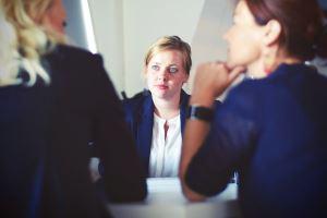 Frau in Gespräch wirkt unsicher, weil sie stottert